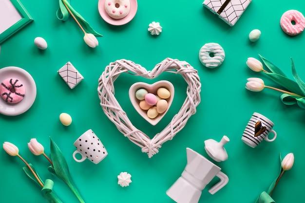 Geometrische frühlingswohnung lag in weiß und grün auf rosa wand. ostern, muttertag, frühlingsgeburtstag oder jahrestag. kunststoff-heizbrett, ostereier, kaffeemaschine, tassen, tulpen, geschenke.
