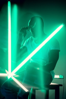 Geometrische linien. filmisches porträt eines stilvollen jungen mannes im neonbeleuchteten raum. helle neonfarben. afroamerikanisches modell, musiker drinnen. jugendkultur im party-, festival- und musikkonzept.