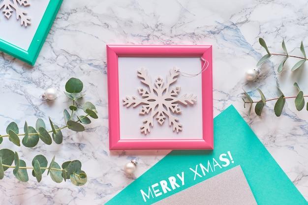 Geometrische weihnachtswohnung lag draufsicht mit rosa und grünen rahmen. frische eukalyptuszweige und dekorative weiße funkelnde schneeflocke im rosa rahmen.