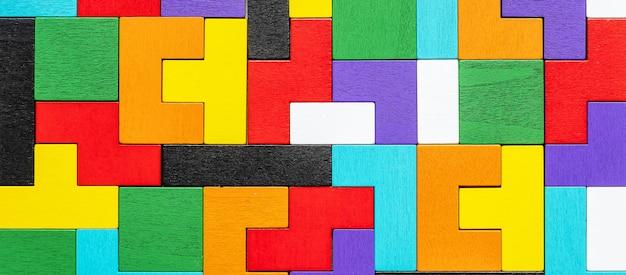 Geometrischer formblock mit buntem holzpuzzleteil.