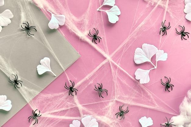 Geometrischer halloween-hintergrund mit weißen ginkgoblättern, spinnennetz und spinnen auf rosa und bastelpapier.