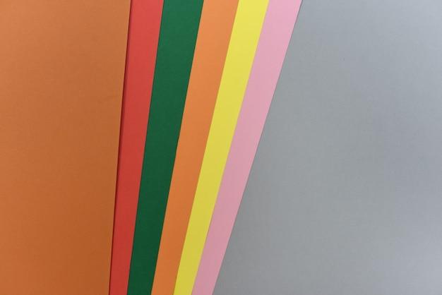 Geometrischer hintergrund mit strukturiertem farbpapier, graue basis mit braun und orangen
