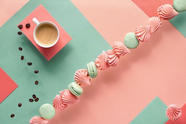 Geometrischer papierhintergrund in minz- und korallenfarben mit kaffee und süßigkeiten