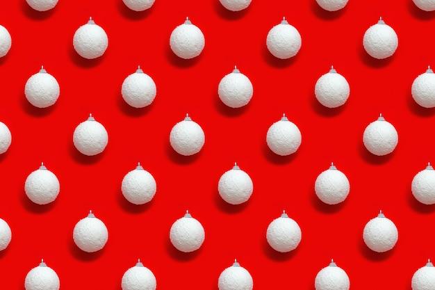 Geometrisches weihnachtsmuster mit weißen kugeln vom schnee auf rot
