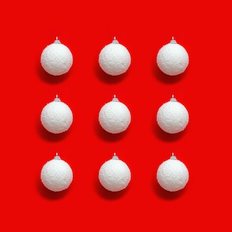 Geometrisches weihnachtsmuster mit weißen kugeln vom schnee auf rotem papier