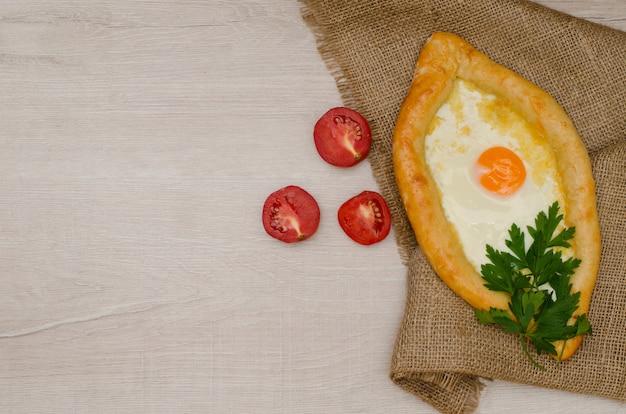 Georgian khachapuri mit käse und eiern auf sackleinen, tomaten
