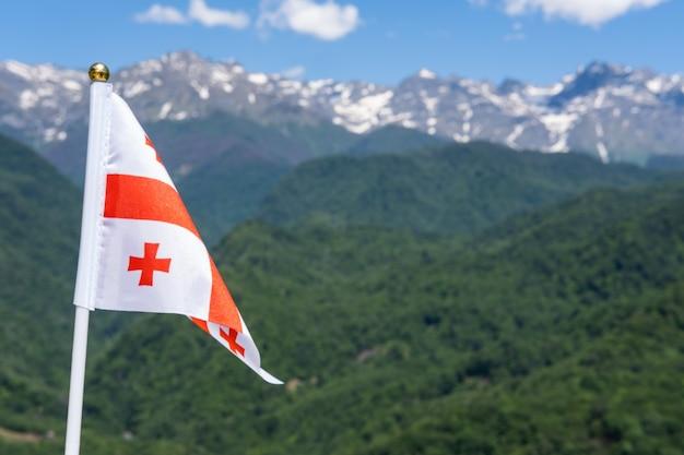 Georgien fahnenschwingen auf dem hintergrund der berge und des blauen himmels georgische nationalflagge
