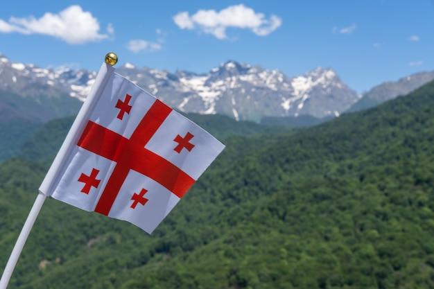 Georgien fahnenschwingen auf dem hintergrund der berge und des blauen himmels
