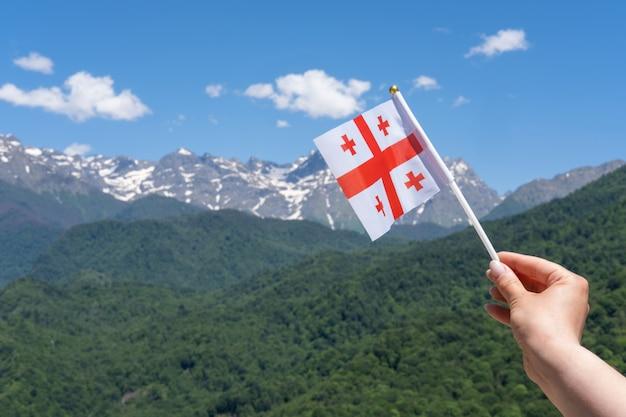 Georgische flagge in der hand der frau auf dem hintergrund der berge und des blauen himmels