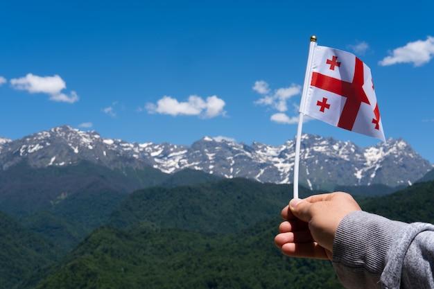 Georgische flagge in der hand des mannes auf dem hintergrund der berge und des blauen himmels georgische nationalflagge
