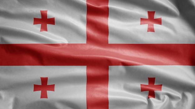 Georgische flagge weht im wind. nahaufnahme von georgia banner weht, weiche und glatte seide. stoff textur fähnrich hintergrund.