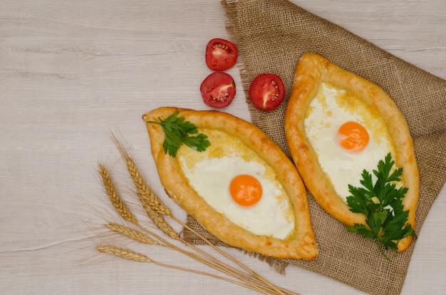 Georgische käsetorte und eier auf sackleinen, weizenähren und tomaten