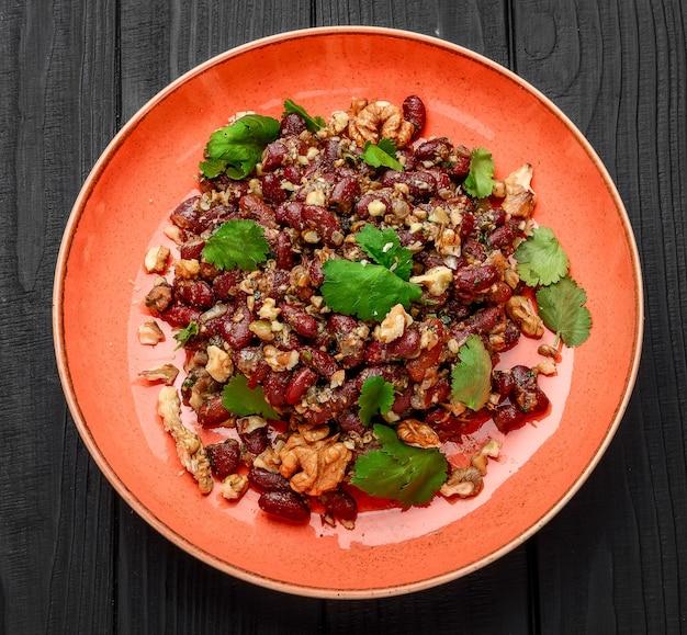 Georgische küche. lobio - bohnensalat mit nüssen, knoblauch und gemüse.