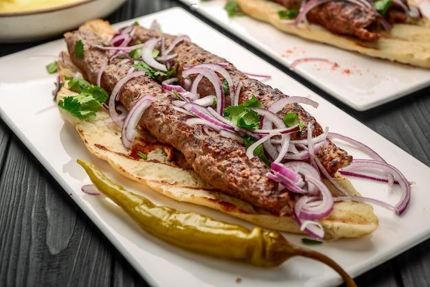 Georgische küche - lulia kebab mit gegrillten zwiebeln, traditionelle georgische küche, auf brot