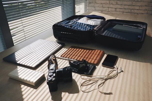 Gepackter koffer, der auf schreibtisch durch fenster mit vorhängen und elektronischen geräten in der nähe liegt