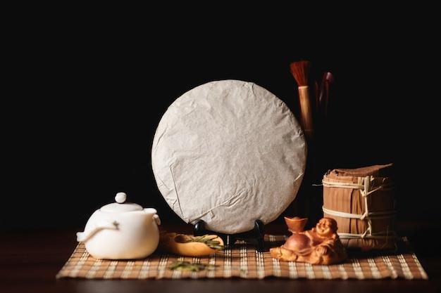 Gepackter pfannkuchen des traditionellen chinesischen puer tees mit weißem teaput und buddha.