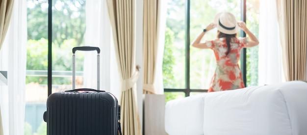 Gepäck im modernen hotelzimmer mit der glücklichen jungen erwachsenen frau, die fast fenster entspannt, asiatische touristin, die zur schönen naturansicht schaut. zeit zu reisen, entspannung, reise, reise und urlaubskonzepte