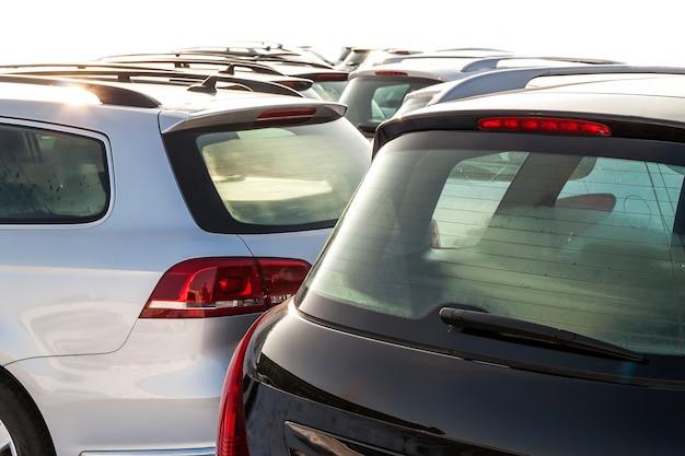 Geparkte autos auf einem grundstück. reihe neuer autos auf dem parkplatz des autohändlers. autos zum verkauf marktthema.