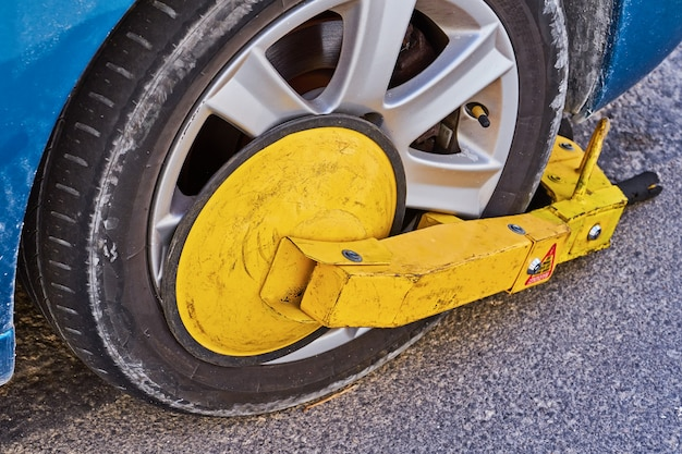 Geparktes auto mit einem wegfahrsperrenreifenschloss von illegal