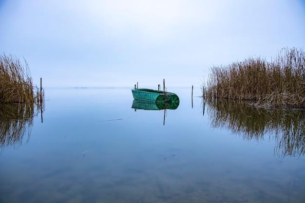 Geparktes leeres boot auf dem see vor sonnenaufgang. landschaft am frühen morgen zum angeln. keine leute