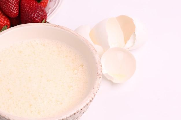 Gepeitscht zu einem schaum die eier in einer schüssel auf einer selektiven weichzeichnung des weißen hintergrundes