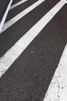 Gepflasterte straße mit weißen fahrbahnmarkierungen für das transportmanagement, gestrichen mit weißen autofahrbahnmarkierungen