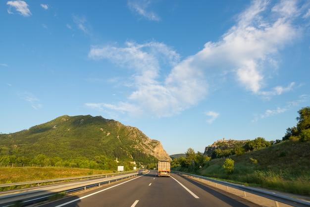 Gepflasterte zweispurige straße in der szenischen alpenlandschaft und im schwermütigen himmel. panoramablick von der auto angebrachten kamera.