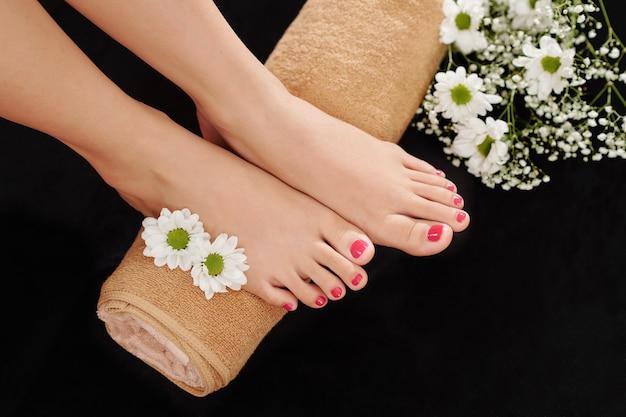 Gepflegte füße auf gerolltem handtuch