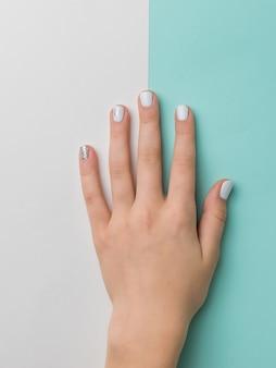 Gepflegte hand mit schönem make-up auf einem blauen und weißen hintergrund. hände pflegen.