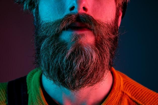 Gepflegter bart, haut, nahaufnahme. porträt des kaukasischen mannes auf gradientenstudiohintergrund im neonlicht. schönes männliches modell mit hipster-stil. konzept der menschlichen emotionen, gesichtsausdruck, verkauf, anzeige.