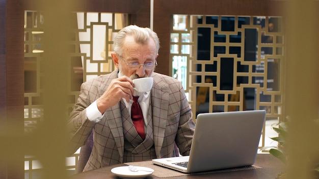 Gepflegter, eleganter, stilvoller, modischer und bärtiger alter verleger, schriftsteller, unternehmer, regisseur, gekleidet in eine elegante jacke, in einem restaurant an einem laptop sitzend und tee und kaffee trinkend