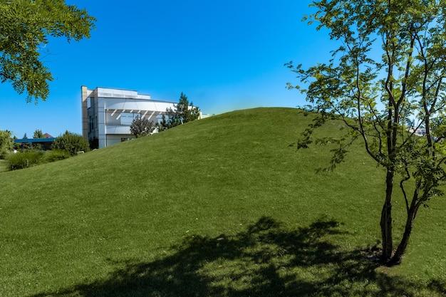 Gepflegter innenhof der luxusvilla mit hügel, der im sommer mit grünem gras bedeckt ist