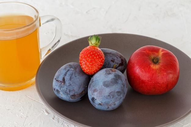 Gepflückte reife pflaumen, ein apfel, eine erdbeere auf dem teller und eine tasse tee auf dem weißen strukturierten hintergrund. nur geerntete früchte.