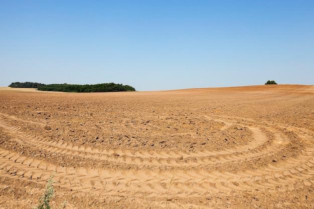 Gepflügtes land, sommer - gepflügtes land auf dem landwirtschaftlichen feld nach getreideernte, traktorspuren am boden
