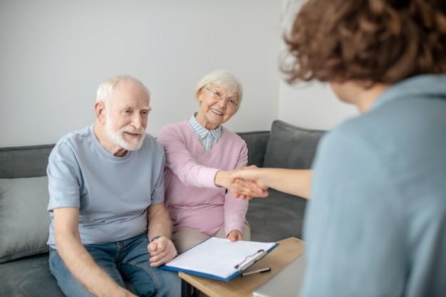 Geplanter termin. älteres paar, das versicherungsvertreter trifft und beteiligt schaut