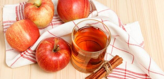 Gepresster apfelsaft im glas mit küchentuch und äpfel mit zimt im hintergrund