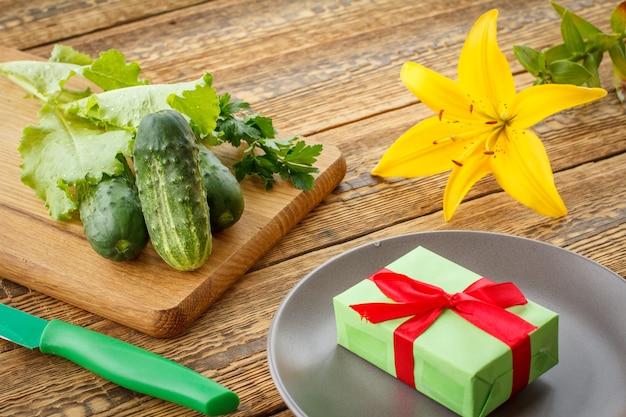Gerade gepflückte gurken und grüner salat auf schneidebrett, messer, teller mit geschenkbox und lilienblume auf alten holzbrettern. gerade geerntetes gemüse. ansicht von oben.
