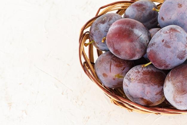 Gerade gepflückte reife pflaumen in einem weidenkorb auf dem weißen strukturierten hintergrund. nur geerntete früchte. ansicht von oben.
