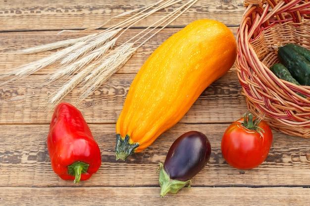 Gerade gepflückte zucchini, aubergine, tomate und paprika mit einem weidenkorb und weizenähren auf alten holzbrettern. gerade geerntetes gemüse. ansicht von oben.