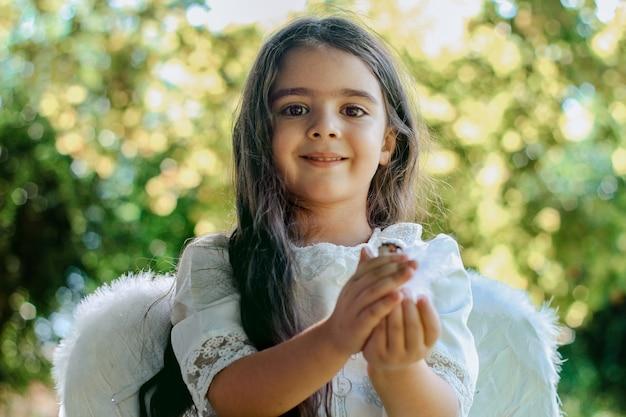 Gerade getauftes kleines christliches mädchen in engelskleidung, das im garten sitzt und lächelt