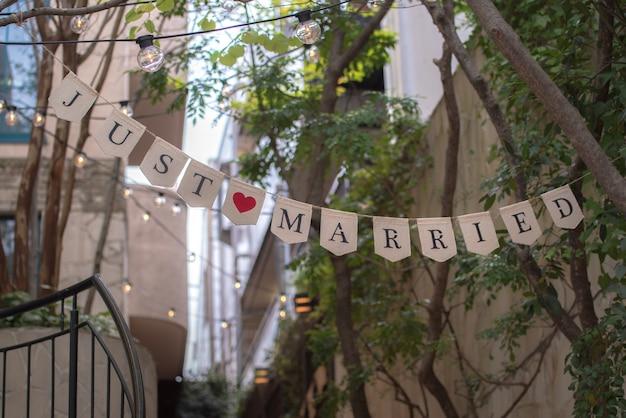 Gerade verheiratete zeichenpartyflagge mit rotem herzen im garten