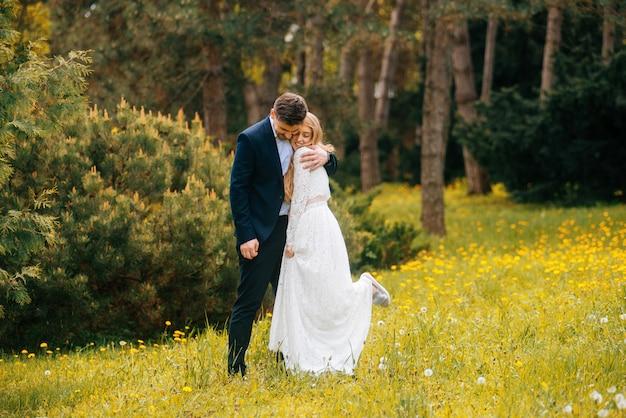 Gerade verheiratetes paar, das spaß im freien im park hat, schöne braut und bräutigam. die braut hat ein bein vom glück gehoben.