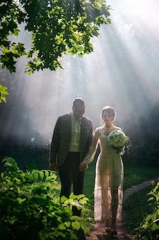 Gerade verheiratetes paar in schönen magischen wald. hochzeitsfotoshooting