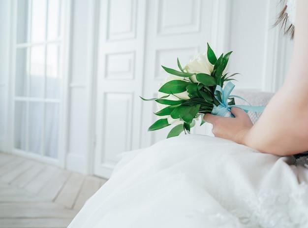Gerade verheiratetes paar mit blumenstrauß von weißen rosen im studio