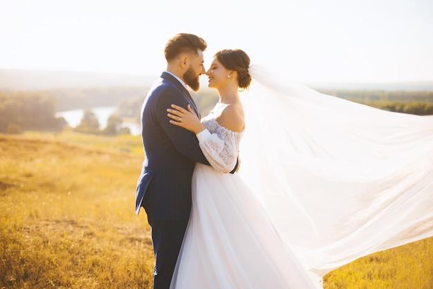 Gerade verheiratetes paar steht auf einem sommerfeld, umarmt und genießt sich im sonnenlicht.
