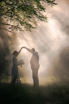 Gerade verheiratetes paar tanzt in schönen magischen wald. hochzeitsfotoshooting