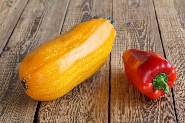 Gerade zucchini und rote paprika auf alten holzbrettern gepflückt. gerade geerntetes gemüse.