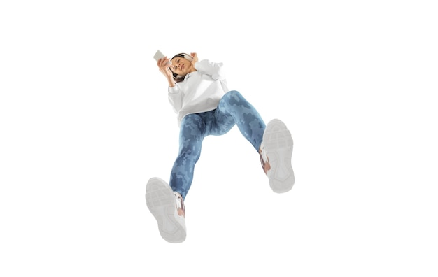 Gerät. junge stilvolle frau im modernen streetstyle-outfit isoliert auf weißer oberfläche, von unten geschossen. kaukasisches modisches modell in schuhen und overalls, musiker, rapper.