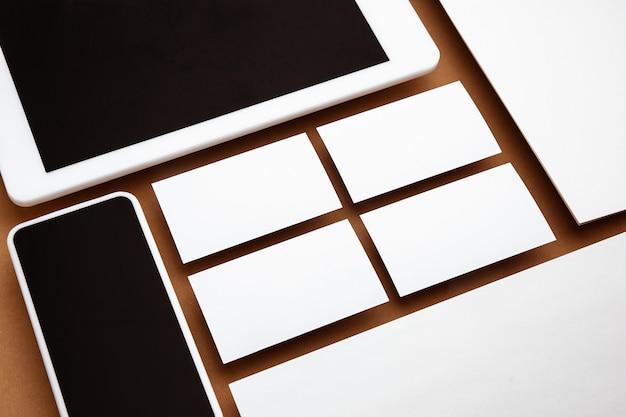 Gerät mit leerem bildschirm, der über braunem hintergrund schwebt. telefon, tablet und karten. modernes mockup im bürostil für werbung. leeres weißes exemplar für design-, geschäfts- und finanzkonzept.