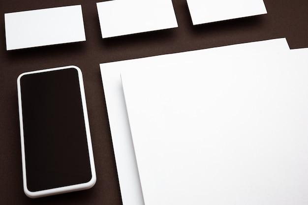 Gerät mit leerem bildschirm, der über braunem hintergrund schwebt. telefon und karten. modernes modell im bürostil für werbung, bild oder text. leeres weißes exemplar für design-, geschäfts- und finanzkonzept.